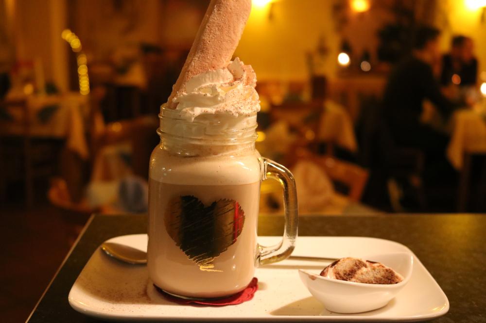 Café al Tiramisu... Kaffee mit Eierlikör, Amaretto, Mascarpone, Milch und Sprühsahne, mit Bisquit und Kakao garniert