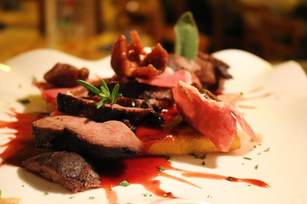 Tranchen von der Gänsebrust auf Madeirasauce mit Feigen und Parmaschinken garniert, serviert auf hausgemachter Polenta