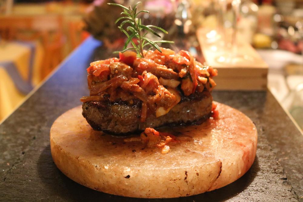 Rumpsteak mit frischen Pfifferlingen, Tomatenstücken und Zwiebeln auf einem persischen Salzblock