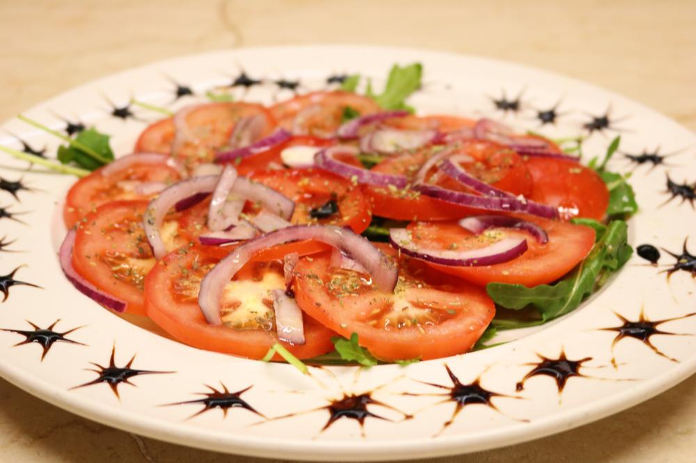Tomatensalat mit roten Zwiebeln, Olivenöl, Oregano und Crema di Balsamico, auf einem Rucolabett