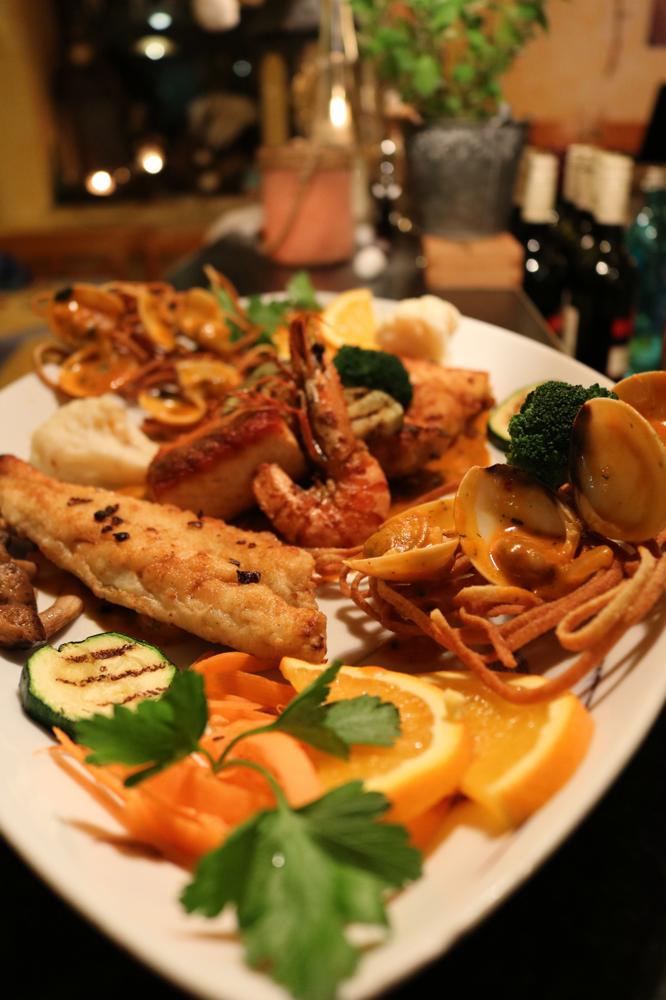 Fischteller mit Scampi, Seeteufel und Lachsfilet auf Hummercreme mit frittierten Spaghettigittern und Venusmuscheln