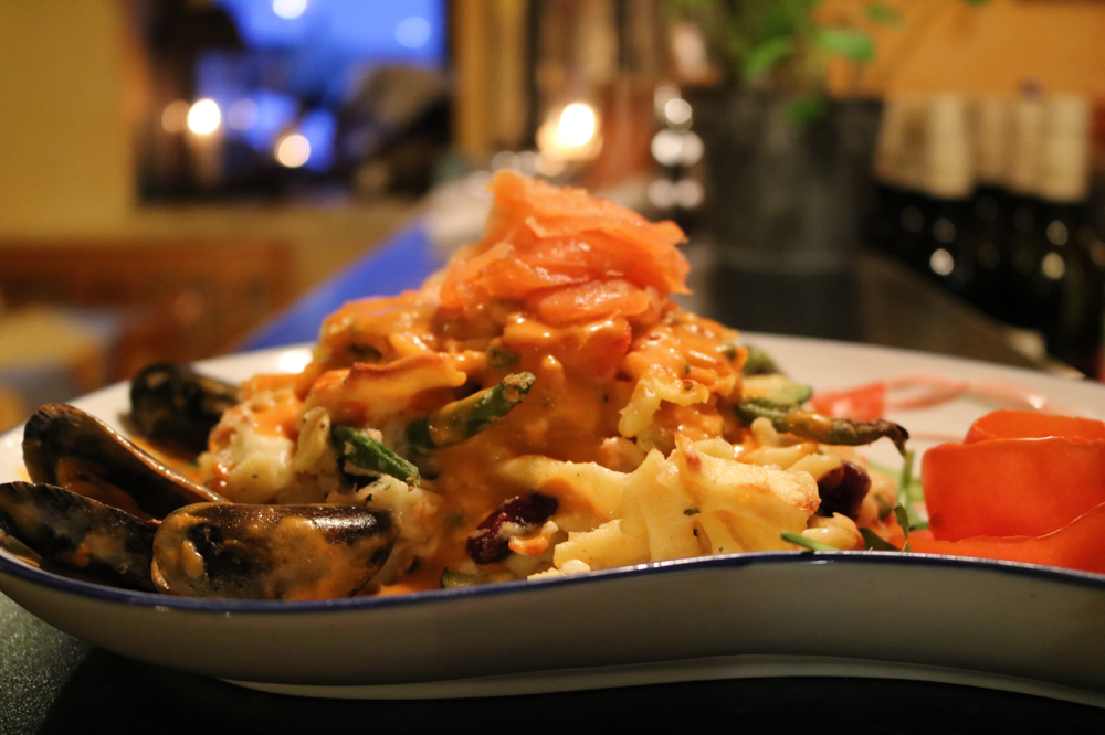Nudelauflauf aus hausgemachten Nudeln, mit Lachsforelle, Gambaretti, Zucchini und grünen Bohnen in Salbei-Sahnesauce, mit Miesmuscheln und Räucherlachs garniert