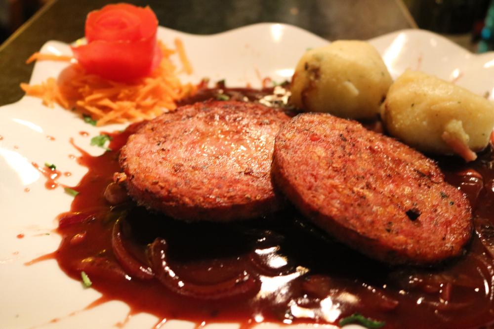 Saumagen auf Zwiebelsauce, serviert mit hausgemachtem Speckknödel