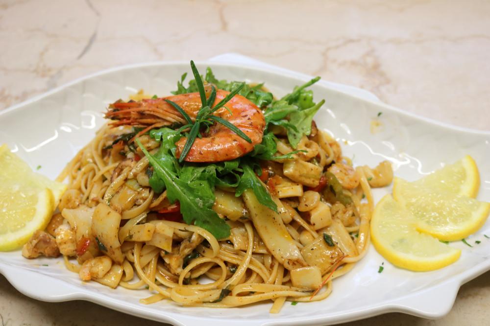 Linguini Marinara mit einem hausgemachten Meeresfrüchtecocktail aus frischem Fisch in leichter Weißweinsauce mit Rucola und Scampi garniert