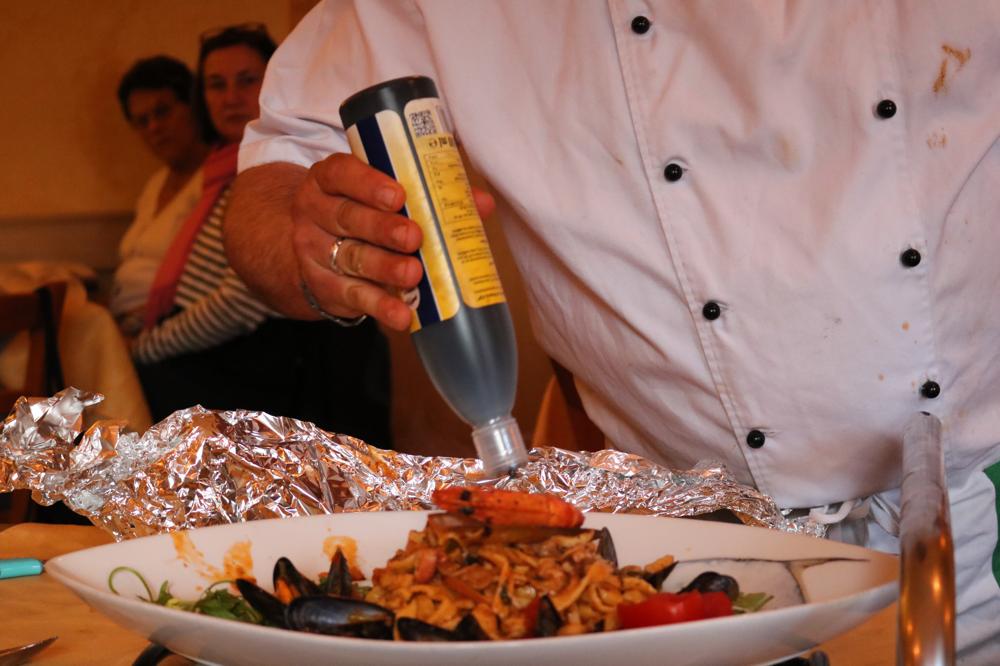 Tagliatelle Mare Monte aus hausgemachtem Nudelteig mit frischen Pilzen und hausgemachtem Meeresfrüchtecocktail in einer leichten mediterranen Sauce mit einem Scampi garniert