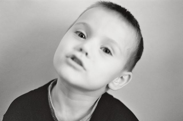 Junge mit leicht gebeugtem Kopf schaut aufmerksam in die Kamera