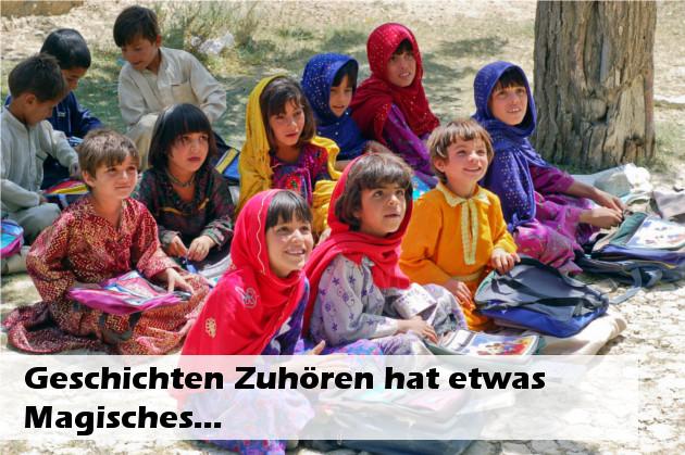 Text: Geschichten zuhören hat etwas Magisches, dahinter Kinder auf dem Boden in bunter Kleidung