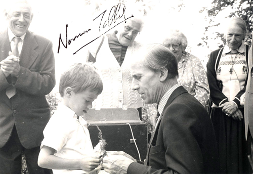 Norman Tebbit attaching a button-hole to Alan Worden, to the delight of Edgar Johns (left)