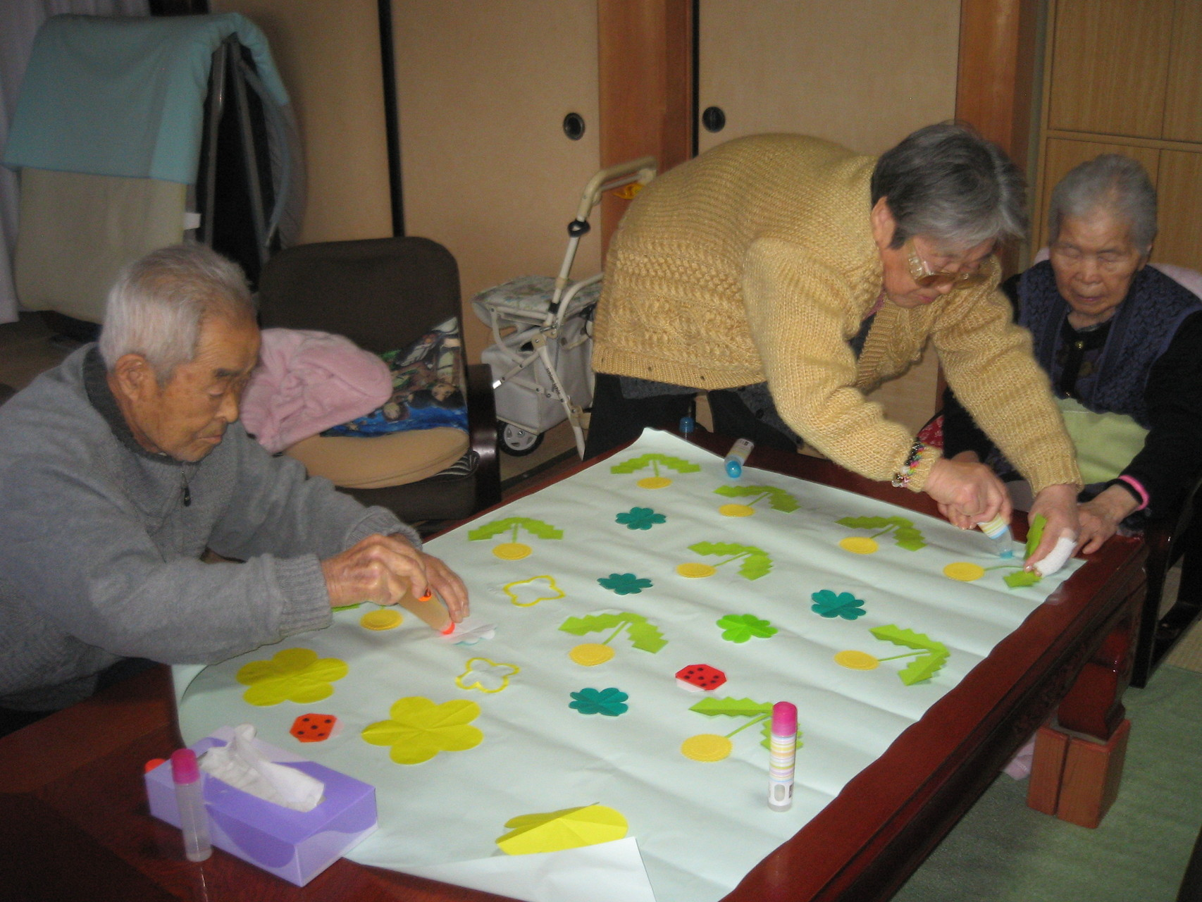 男性も女性も協力しながらタンポポの貼り絵を作っています