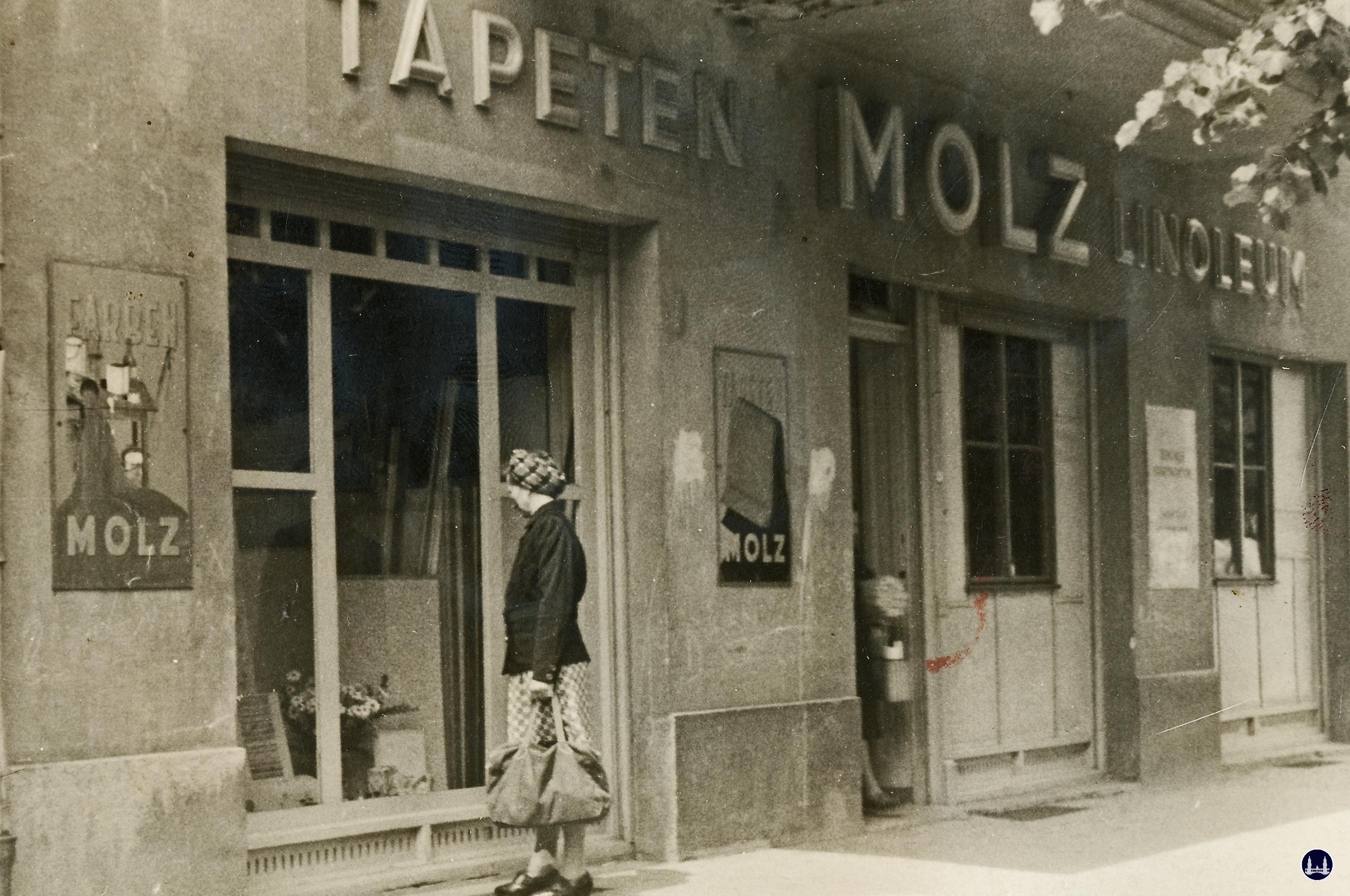 Molz Raumdesign am Mariendorfer Damm. Kundin in der Nachkriegszeit vor dem Schaufenster.