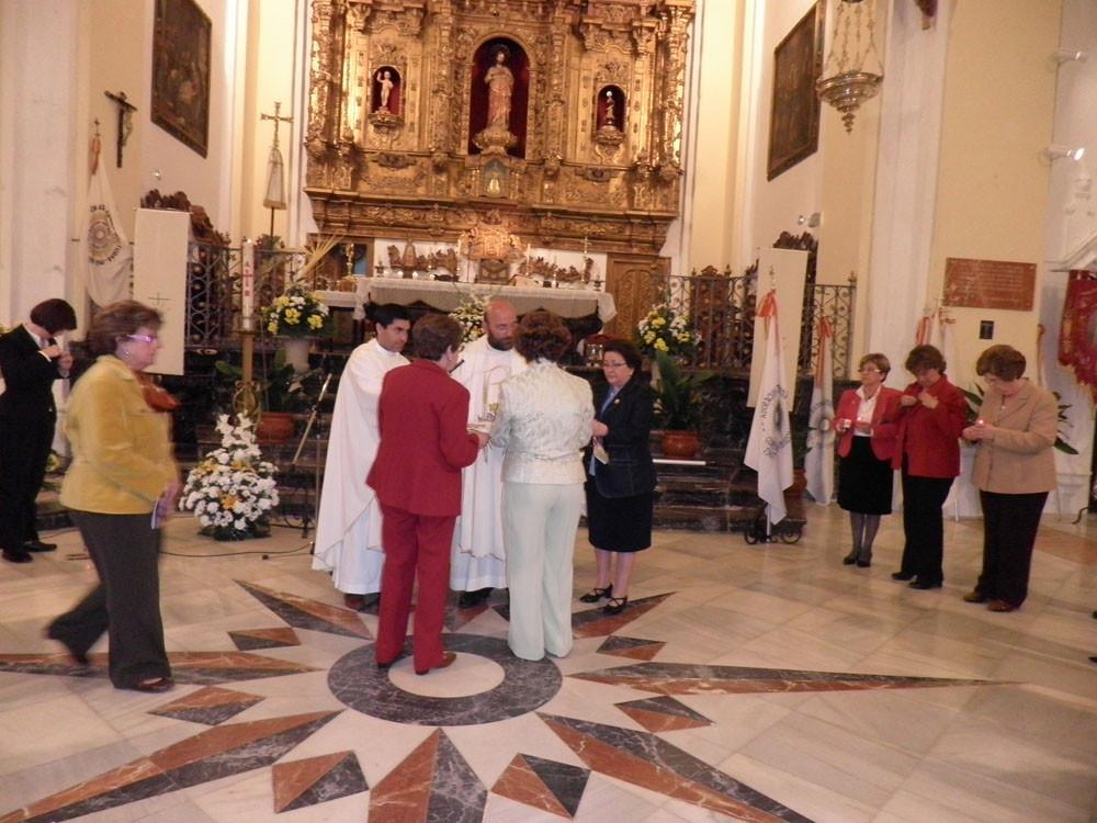 Las adoradoras reciben la insignia mientras la Presidenta Diocesana les hace entrega de una vela