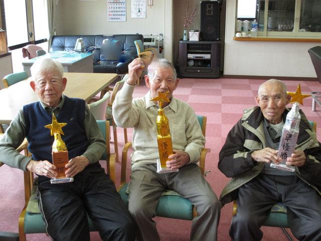 トロフィーを持つ上位3名の男性