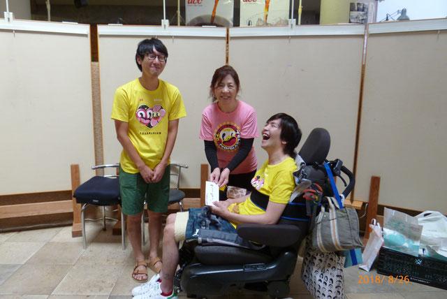 24時間テレビのチャリティTシャツを着て笑う車椅子の男性とその奥で微笑む男性と女性