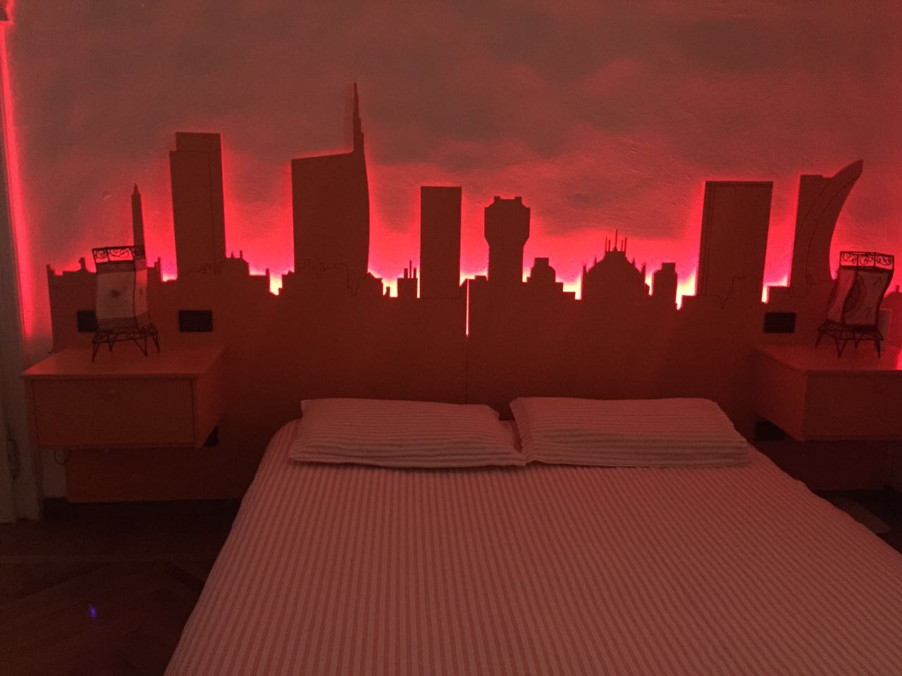 Skyline di Milano con luce Led per cromoterapia. Testaletto con comodini.