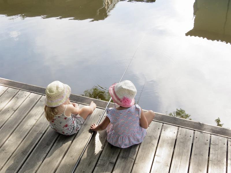 Kinder auf Steg, kleine Mädchen angeln