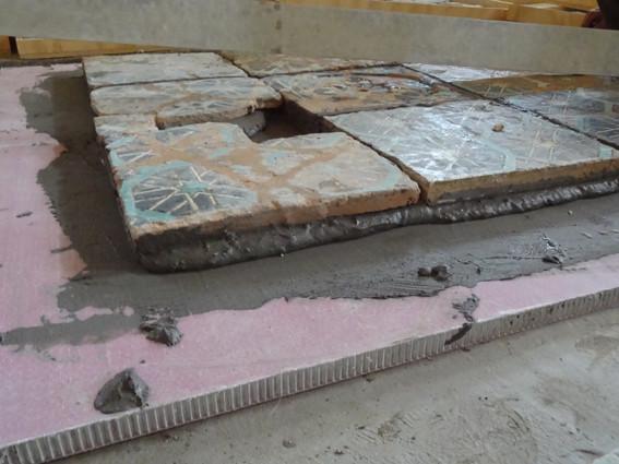 """Vue sur la tranche du panneau nid d'abeille (""""nids"""" gris en aluminium et surface en résine rose) et des carreaux (Socra, 2013)"""