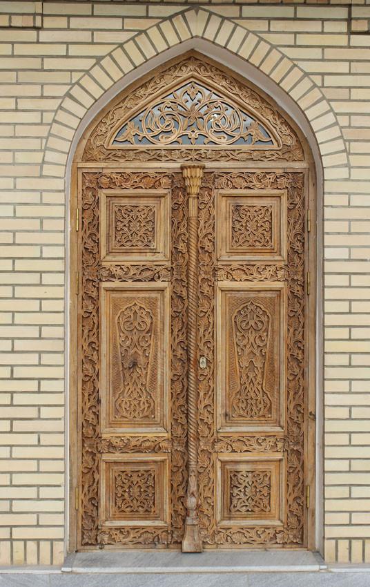 Porte d'entrée du bâtiment. Ces panneaux de bois sculpté, art typique ouzbek, ont aussi été réalisés par une entreprise locale (Ollagnier, 2014)