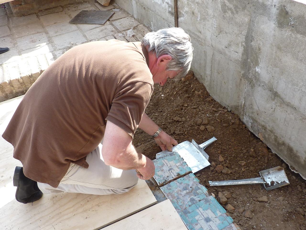 Dépose d'un carreau. Ici l'absence de mortier facilite le décollage de la terre (Socra, 2012)