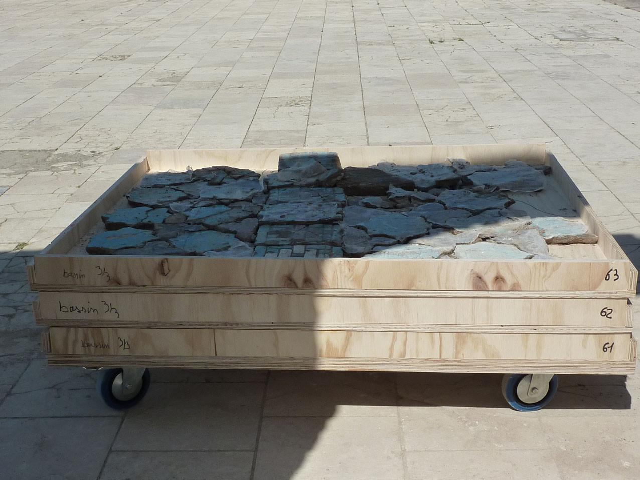 Bacs posés sur une planche à roulettes pour le transport au musée (Socra, 2012)