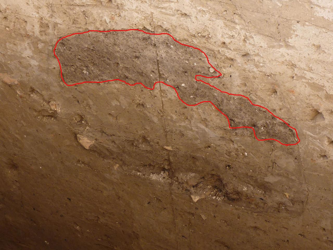 """Dans la tranchée n°2 un fragment de four (couleur sombre, entouré de rouge) a été utilisé comme remblai pour l'installation du pavement. Les fours pour la céramique devaient être changés régulièrement, d'où leur présence dans les """"poubelles"""" (Socra, 2012)"""