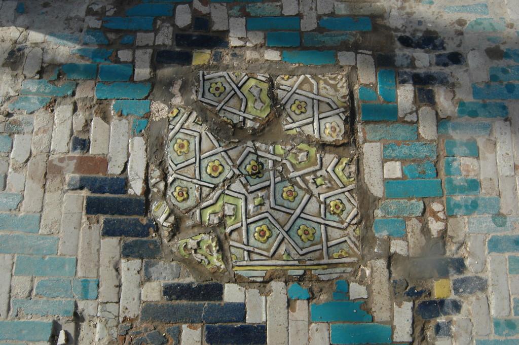 Fragments d'un carreau de céramique glaçurée à décor polychrome en relief, qui ne semble pas être en place, ou du moins pas à la place à laquelle il était originellement destiné (photo : M.Schvoerer, 2008)