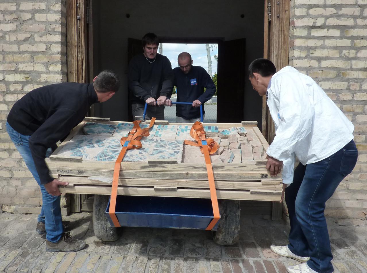 Transport des bacs avec les carreaux restaurés jusqu'au chantier (Socra, 2013)