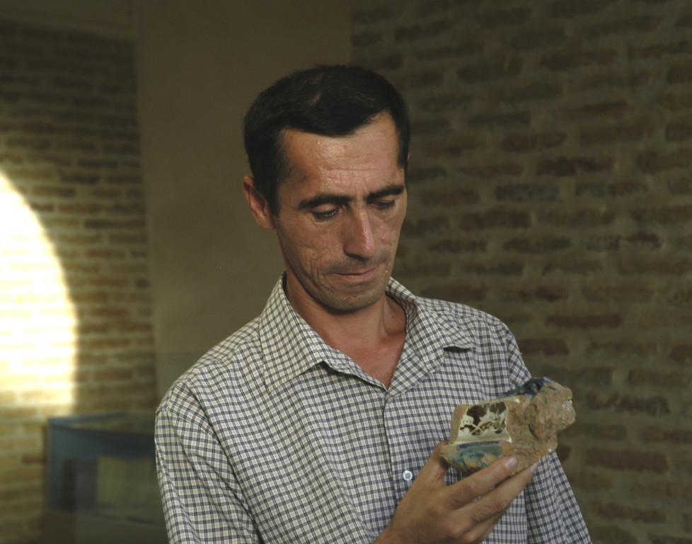 Bahodir Mamadiev, directeur du Musée d'Histoire de Karshi avec un fragment de céramique glaçurée à décor de lustre métallique du XIVème s ap J.C. (photo : C.Ollagnier, 2008)
