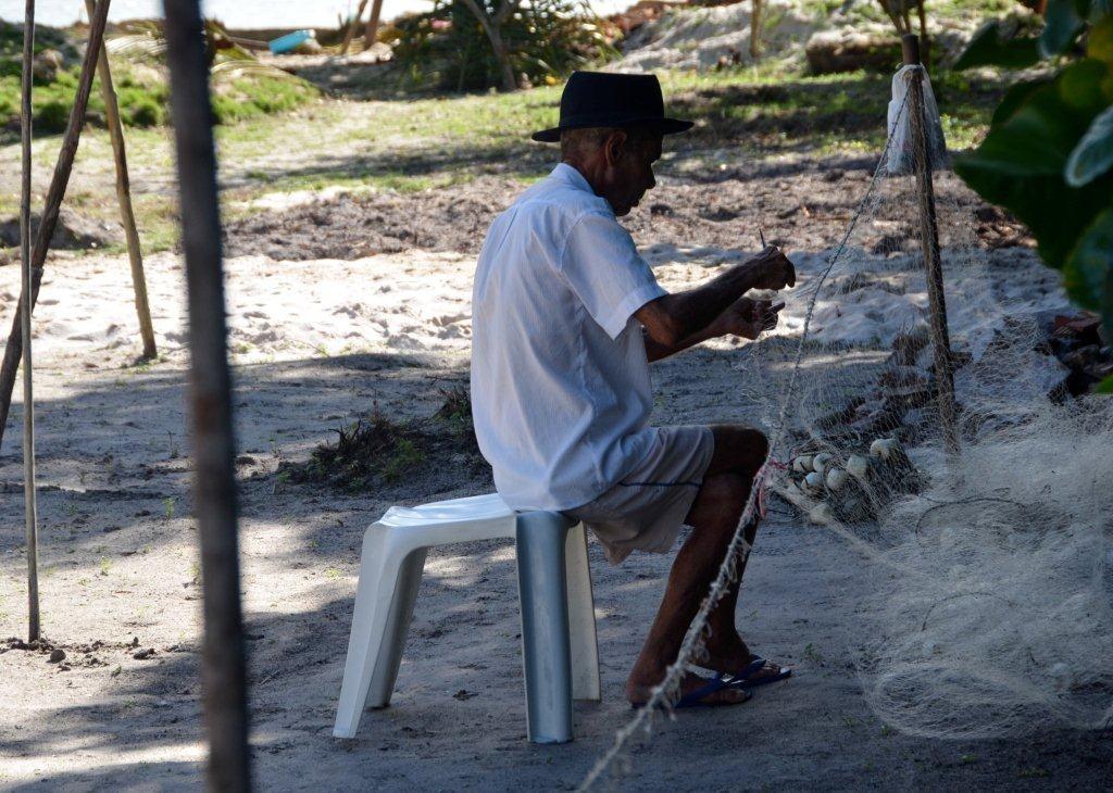 Fischer beim Netzeflicken im Dorf Sapinho