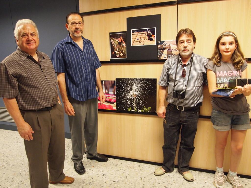 El jurat i la premiada infantil, amb les fotografies premiades