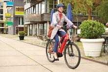 Frau fährt auf Raleigh e-Bikes durch die Innenstadt