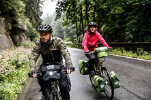 Pärchen fährt auf seinen e-Bikes mit den wasserfesten Taschen von Ortlieb über eine Waldstraße