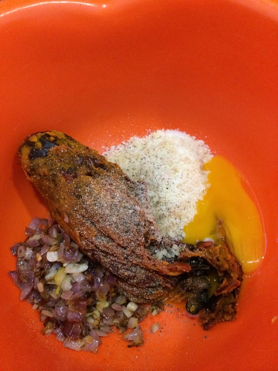 Die Kürbismasse mit zu dem gedünsteten Zwiebeln (oder Lauch) und dem Eigelb geben