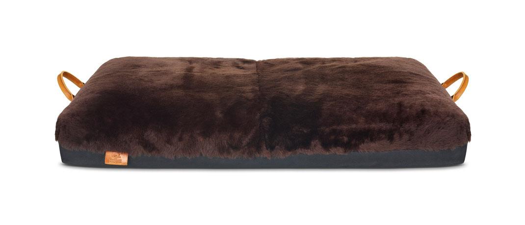 Braunes Hundebett mit Schaffell überzogen und ledernen Griffen an den Seiten