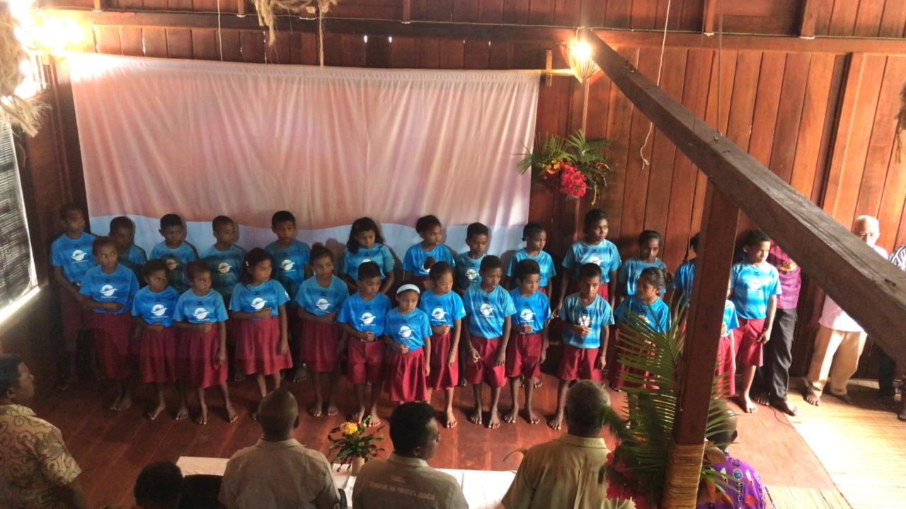 """Die Schūlerinne und Schūler singen traditionsgemāss das lied """"Tanah Papua"""" (Das Land von Papua)"""
