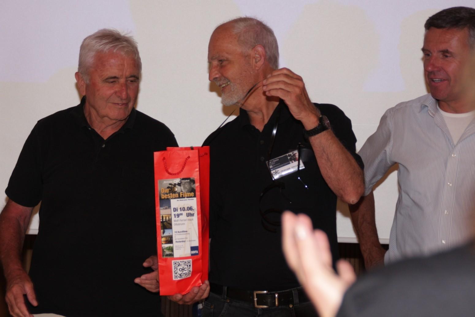 Johann Weber erhält vom Clubleiter ein mit Super-8 Streifen verpacktes Geschenk