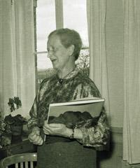 Emma Brendel steht mit einem Buch in der Hand vor ihrem Fenster.