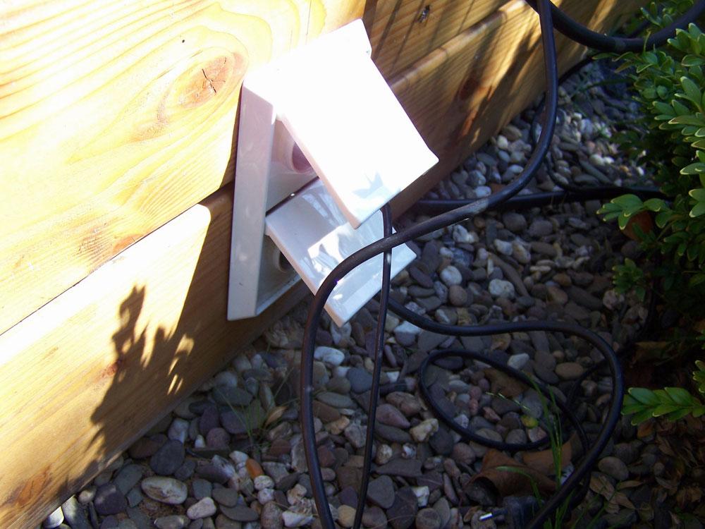 Steckdose in einer Holzwand. Die Steckdose kann im Garten als Trennwand, Gartenhaus oder auch Holzliege ausgebildet sein. Zum Einstecken von Strom- und Lampenkabeln ist diese wassergeschützte Steckdose bestens geeignet.