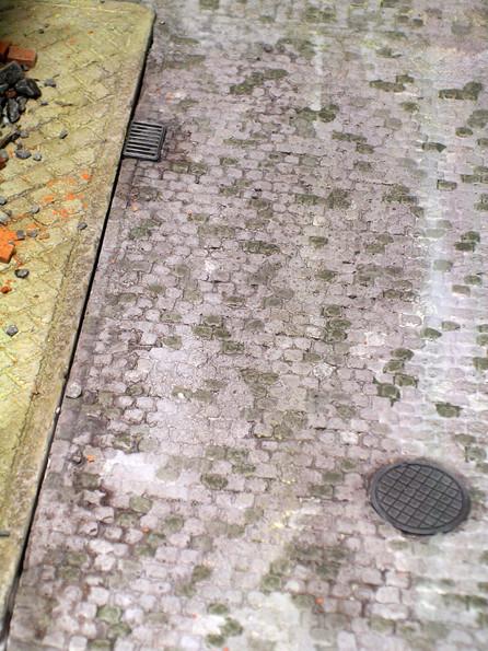 Das Straßenpflaster wurde in mehreren Farbtönen bemalt, dann erfolgte ein Washing und Trockenbemalung. Beachte die versenkten Kanal- und Abwasserdeckel.