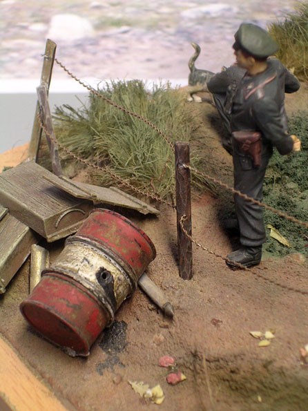 Stacheldraht, Ölfass und Munitionskisten zeigen Spuren eines Gefechtes.