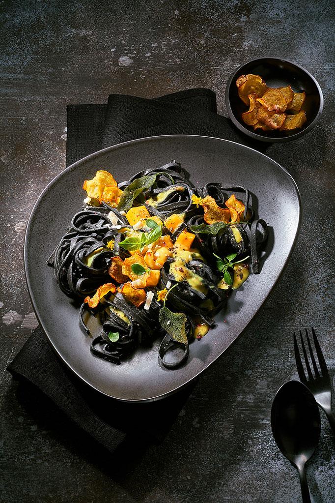 Nudeln negro, schwarze Nudeln mit fruchtigem Topping auf dunklem Untergrund. Rezeptfotografie