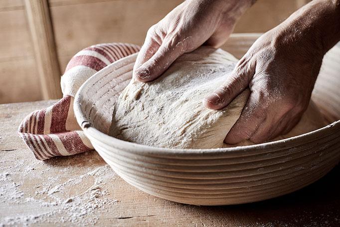 Brotteig für die Bäckerei Kiepenkerl. Hand walkt Teig in alter traditioneller Holzschale.