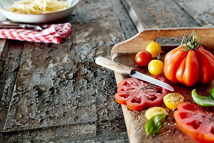 Food Still mit Gestaltungsfläche(copy space) alte Tomatensorten geschnitten. Konzept rustikal italienisch