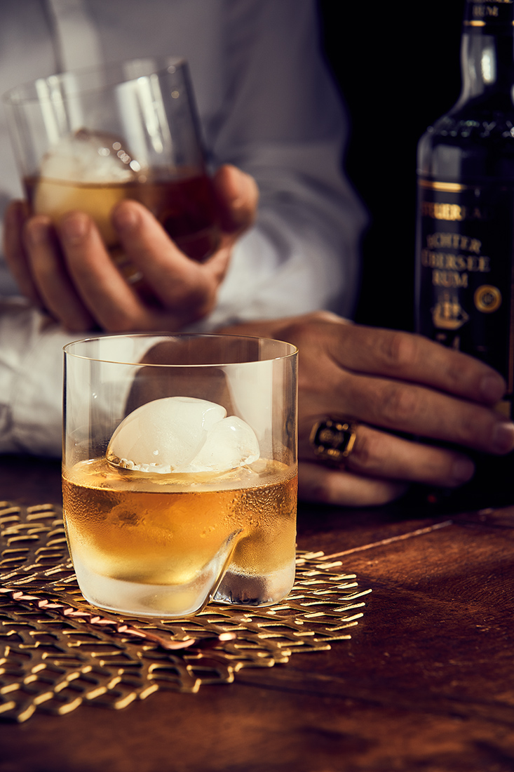 Rum on the Rocks. Rum oder Whiskey mit rundem Eiswürfel, Werbefotografie,Zeitungsanzeige Team Reiter