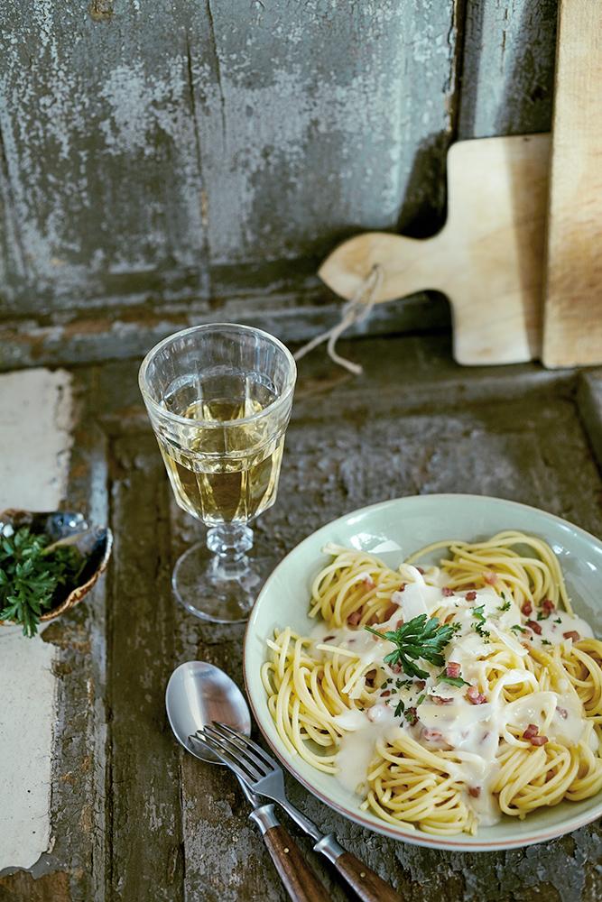 Pasta mit Käse Sahne Sauce und Schinkenstückchen. Konzept rustikal italienisch