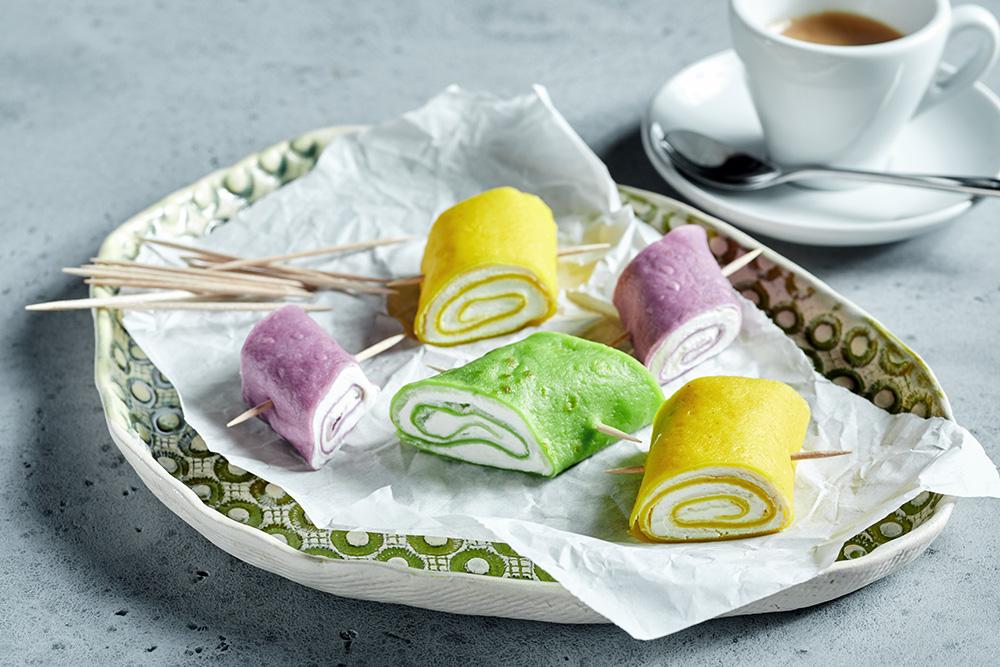 farbige gefüllte Pfannkuchenröllchen als Apetizer.