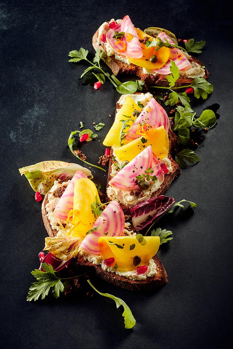 Arrangement aus Brot belegt mit farbigen Beete-Sorten. Flat lay auf dunkelm Fond, Titelfotografie aus dem Fotostudio team Reiter