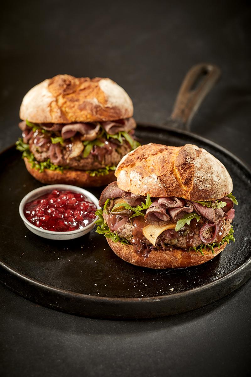 Zwei Wild-Burger BBQ auf schwarzer Pfanne mit Preisselbeersauce