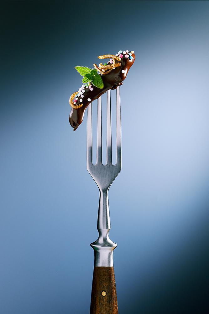 Süße Heuschrecke schokoliert mit Minzblättchen. Buffalo Würmer Insektensnack mit süßen Zuckerpoerlen als Dessert oder Apetizer. Team Reiter fotografiert Insekten Snacks