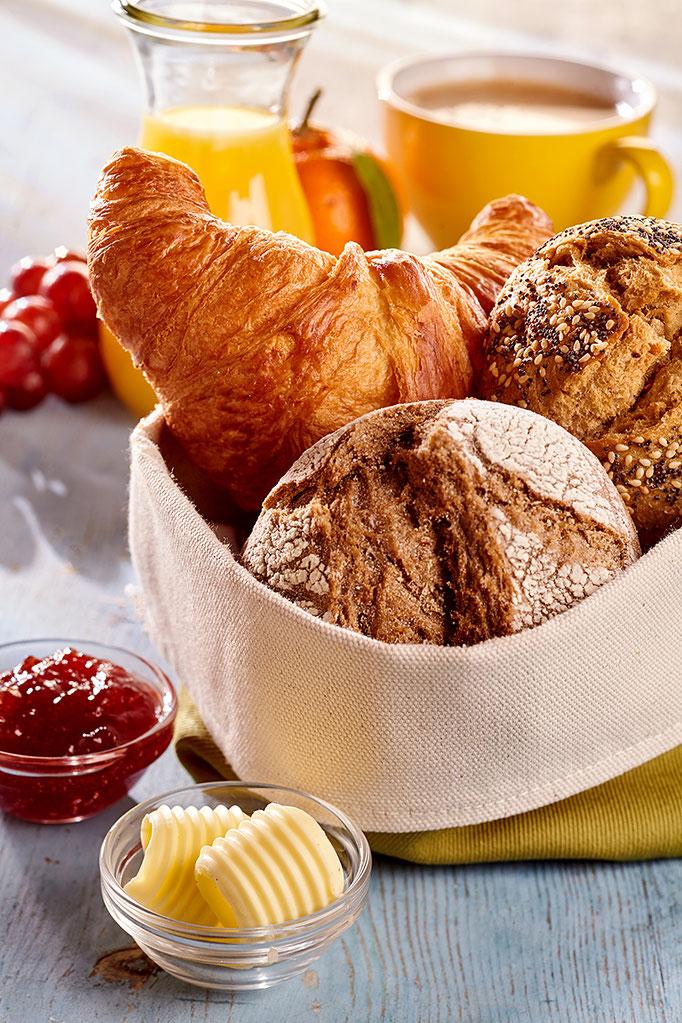 Frühstücksszenerie, frische Brötchen und Fruchtsaft