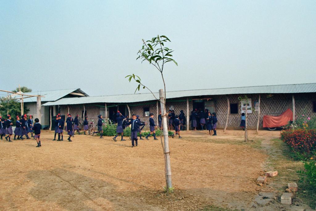 während der Pausen.   Das erste Schulgebäude hatte Wände aus Bambusmatten und Blechdächer